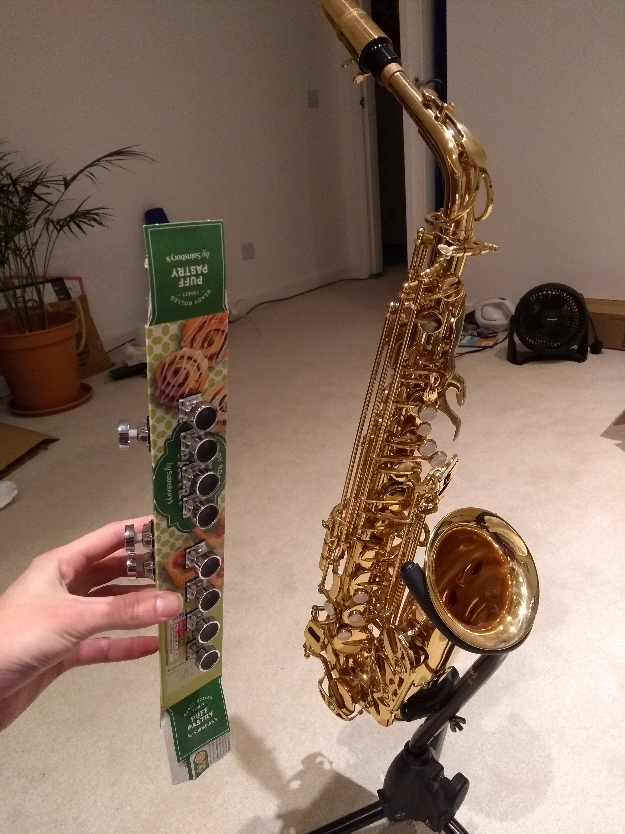 Long pastry packaging with buttons stuck in it, next to an alto saxophone