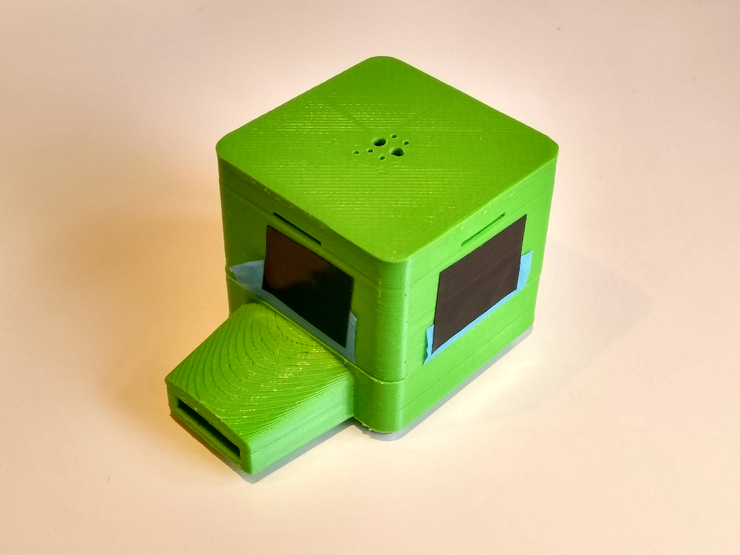 The two halves 3D printed in green, assembled with screws and a nitrile glove membrane