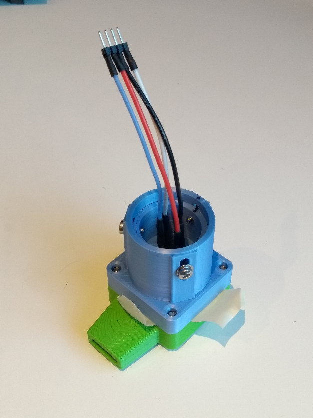 Mouthpiece base with a 3D printed tube on top of it and some wires coming out. There are screws in slots on the side to adjust the height of the sensor.