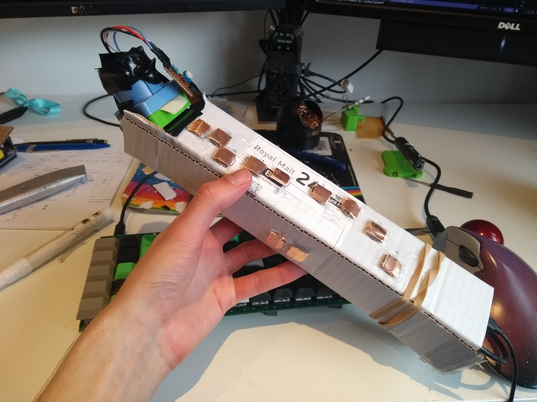 Cardboard cuboid with some copper pads, and a colourful breath sensor at the top end. The tube is held closed with a rubber band.