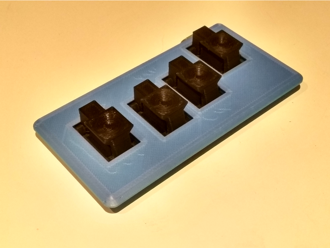 Four switch assemblies mounted to a plate. They're staggered to match my fingers.
