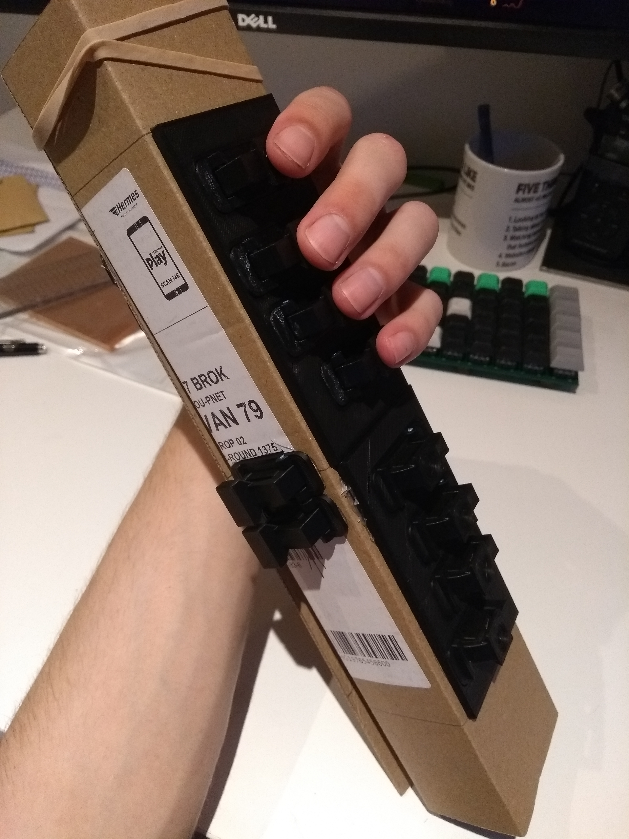 Cardboard cuboid with black 3D printed keys mounted to it.