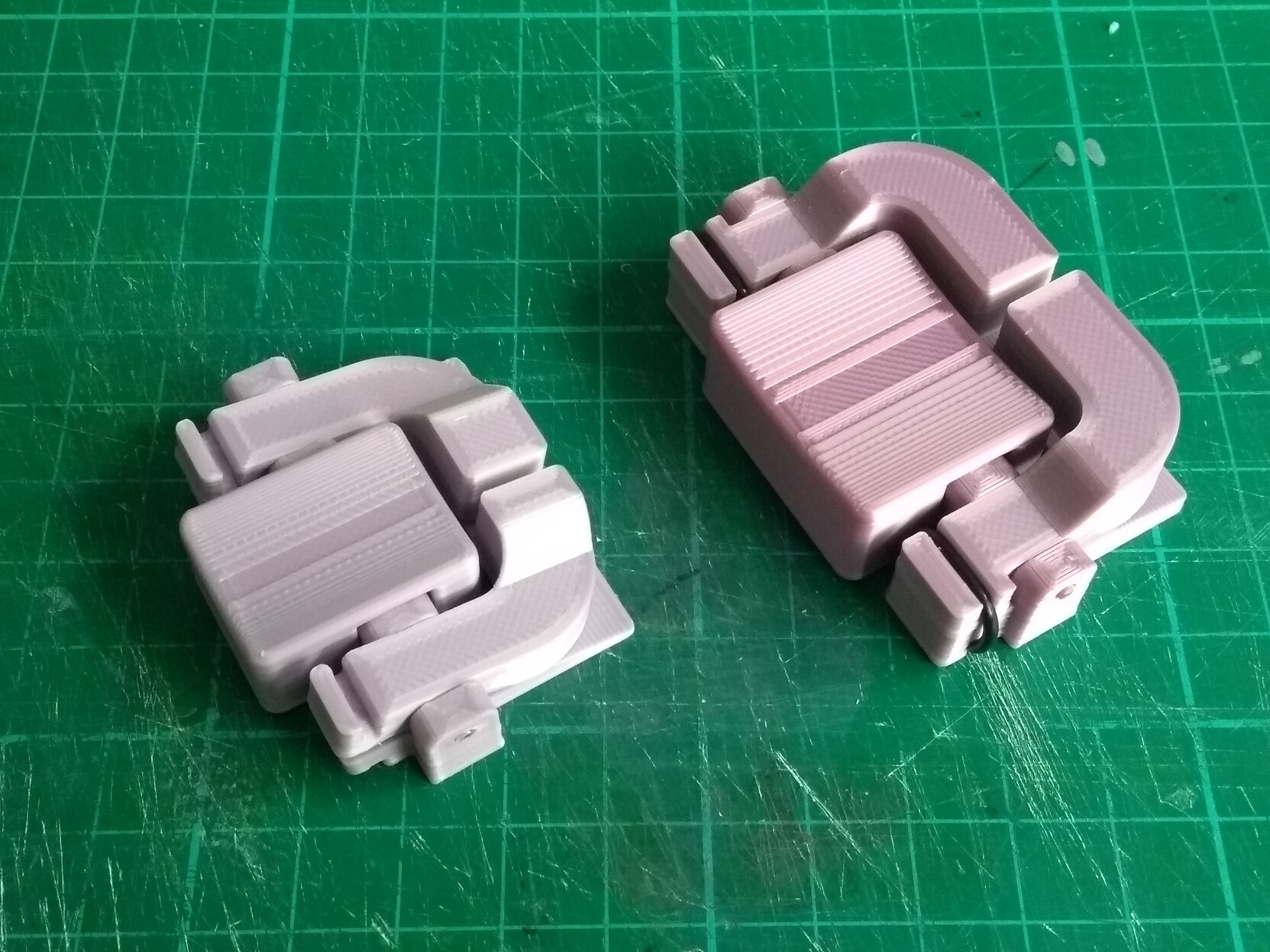 Two 3D printed prototypes of the buttons. The first (left) is smaller and the buttons turned out to be too small. The second is wider and gives more space for you to press the buttons with your thumb, without accidentally pressing both.
